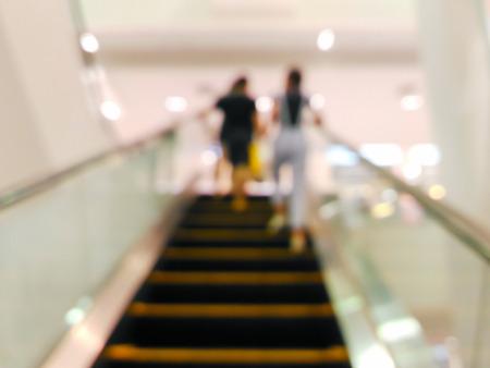 upstairs: Blurred women on escalator going upstairs at department store Stock Photo
