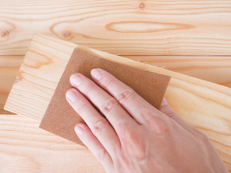 Hand sanding wooden pallet with sandpaper