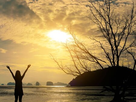 Silhouette woman raising her hands on the beach on dramatic sky background at sunrise Stock Photo