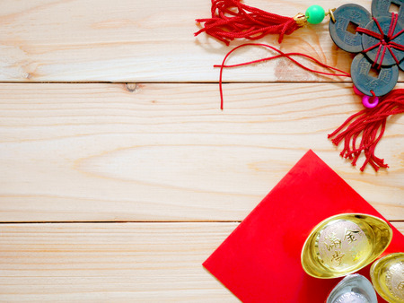 Chinese gold ingots, red packet and ornament for Chinese New Year background. Top view. Copy space. Stock Photo