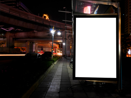 street signs: Blank advertising billboard next to bicycle public system at night Stock Photo