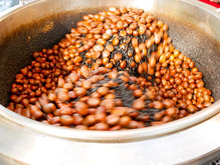 Chinese chestnuts being roasted in big pot Stock Photo
