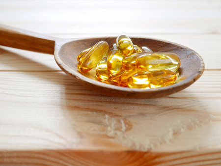 Fish oil capsules on wooden spoon Stock Photo