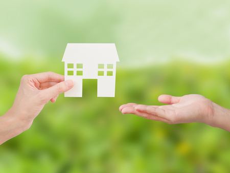 Property agent giving house model to client on front yard background. Property and real estate concept.