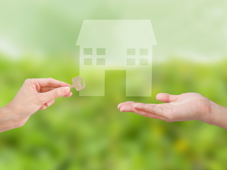 Property agent giving house key to client on front yard background. Property and real estate concept.