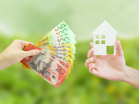 Client giving Australian money to property agent for buying house. Property and real estate concept.