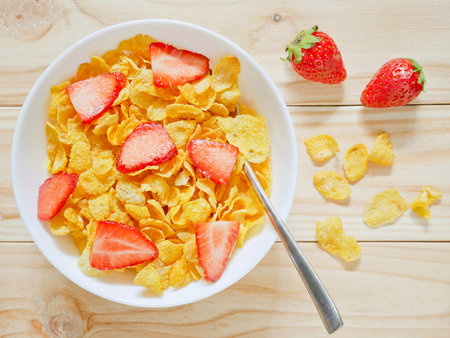 Golden cornflakes cereal with strawberries on wooden background. Top view.
