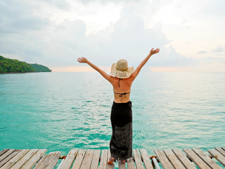 Woman on wooden jetty raising arms to the sky Stock Photo