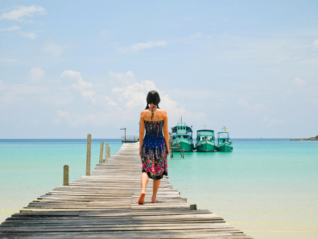 Woman walking on wooden jetty on a sunny day