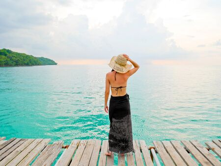 Woman with sunburned back looking at the sea on wooden jetty Stock Photo