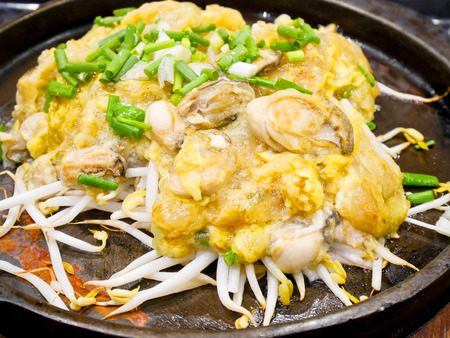 Oyster omelette sizzling in the pan Stock Photo