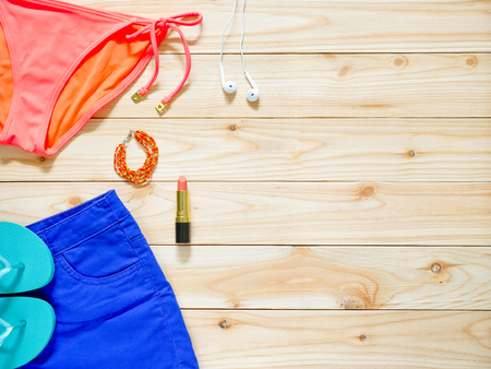 earbud: Womens beachwear and accessories on wooden background. Beach clothing concept.