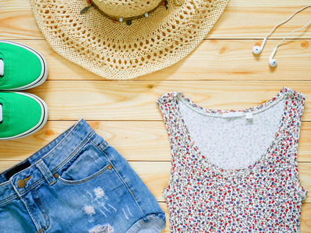 Summer clothing and accessories on wooden background