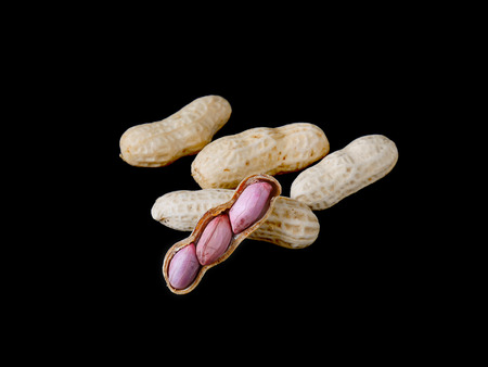 Group of peanuts and peeled peanuts isolated on black background