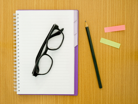 paper sheet: Blank notebook with glasses, pencil and sticky notes on wooden table