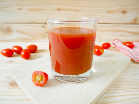 A glass of tomato juice and fresh tomatoes on wooden cutting board