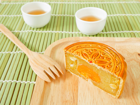 Half of durian mooncake with yolk egg on a wooden plate for Mid-Autumn Festival or Harvest Festival Stock Photo