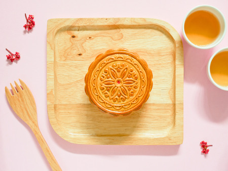 Mooncake on a wooden plate for Mid-Autumn Festival or Mooncake Festival. Top view.