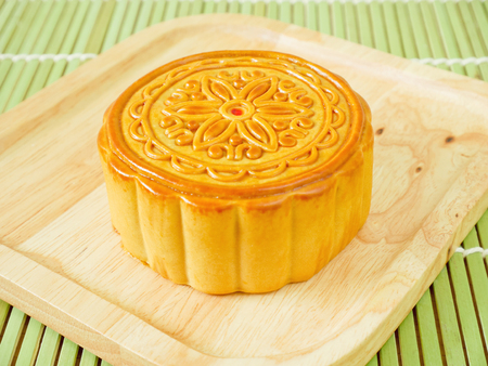 Mooncake on a wooden plate for Mid-Autumn Festival or Mooncake Festival  Stock Photo