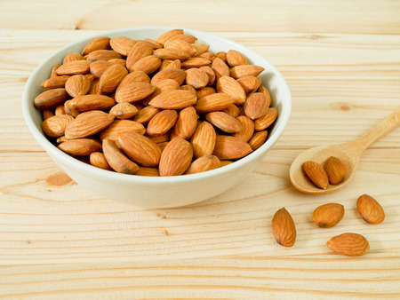Almonds in a bowl on wooden table with copy space