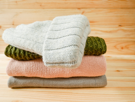 Stack of sweaters and knitted cap on wooden background. Winter clothing concept. Stock Photo