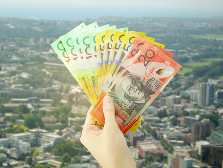 Hand holding Australian money banknote on Sydney cityscape background. Business and finance concept.