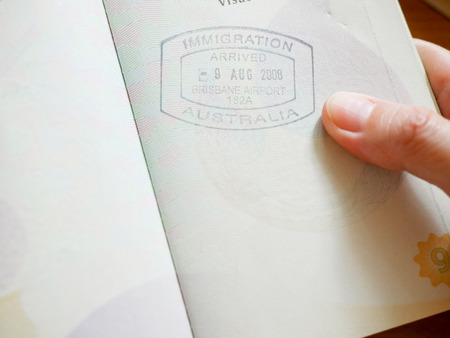Hand holding passport with Australian immigration stamp for entering the country Standard-Bild - 95309293