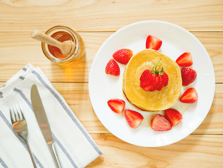 Stack of homemade flourless oatmeal pancakes with fresh strawberry and honey