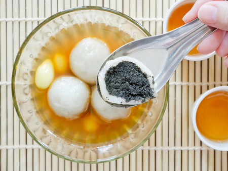 Sweet glutinous rice balls filled with black sesame seeds in sweet ginger syrup (Tang Yuan). Chinese dessert.