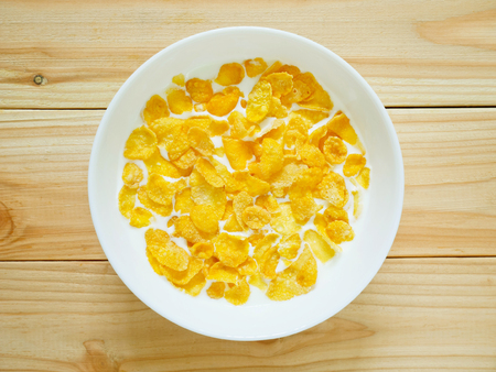 Golden cornflakes breakfast cereal on wooden background. Top view.l Healthy breakfast concept.