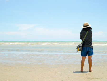 Woman standing on the beach on a sunny day Banque d'images