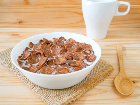 Chocolate breakfast cereal in a white bowl on wooden table. Healthy breakfast concept. 版權商用圖片