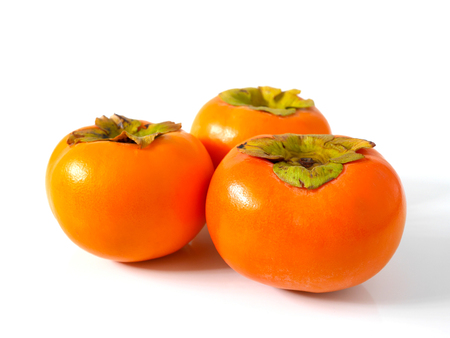 Group of fresh ripe persimmons isolated on white