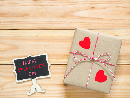 Valentines Day gift box with Happy Valentines Day message on mini blackboard on wooden table. Stock Photo