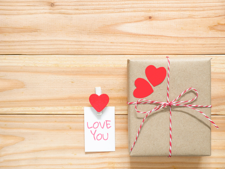 Valentines Day gift box and two paper hearts with greeting card on wooden table. Copy space. Top view.