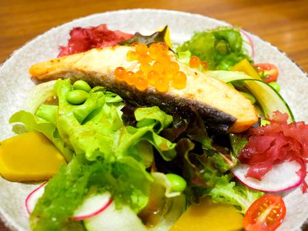 Köstlicher gegrillter Lachssalat auf Holztisch Standard-Bild