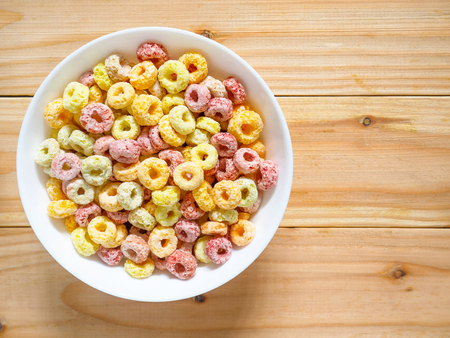Colorful fruity breakfast cereal in a bowl on wooden  with copy space. Top view. Stockfoto - 121626189
