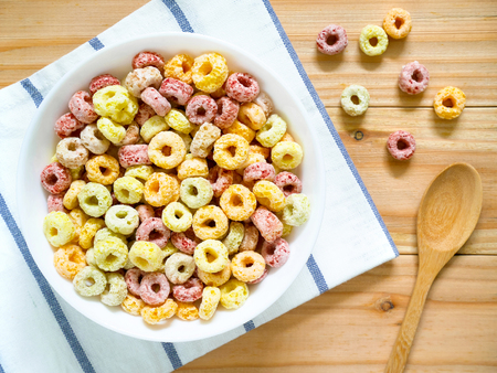 Colorful fruity breakfast cereal in a bowl on wooden