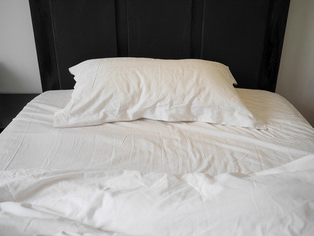 Unmade bed with crumpled duvet, bed sheet and pillows at the hotel in the morning Reklamní fotografie