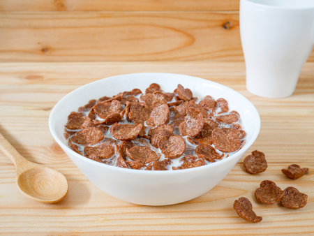 Chocolate breakfast cereal in a white bowl on wooden table. Healthy breakfast concept. Reklamní fotografie