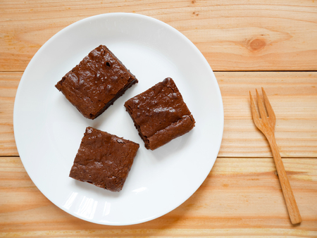 Homemade chocolate brownies on a white plate with wooden fork. Top view. 스톡 콘텐츠