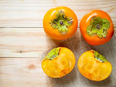 Fresh ripe persimmons on wooden Stockfoto
