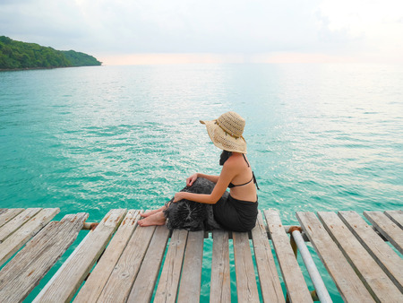 Woman in bikini with straw hat sits on wooden jetty while looking at the sea