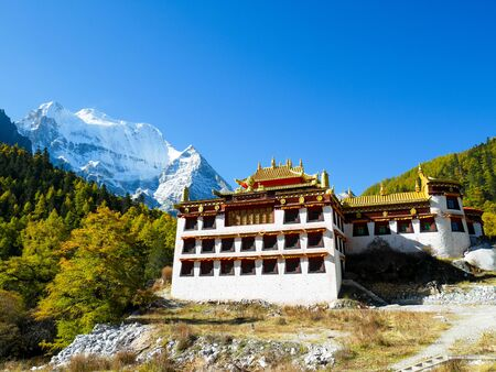 Chonggu monastery with snow capped mountains in Yading Nature Reserve, Sichuan, China