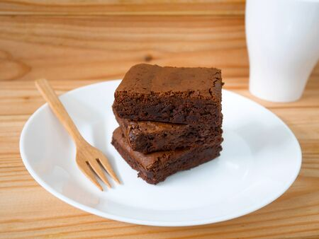 Stack of homemade chocolate brownies with wooden fork on a white plate