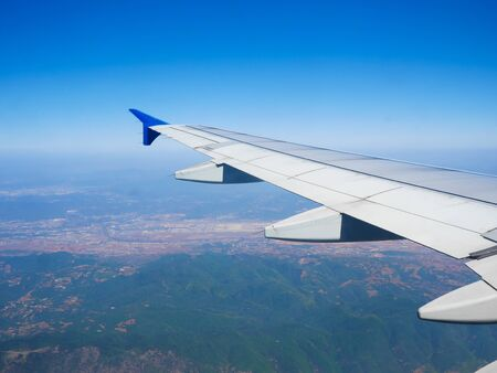 View of airplane wing, blue skies and the land during landing.