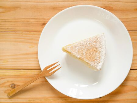 A piece of homemade yogurt cake with icing sugar on a white plate