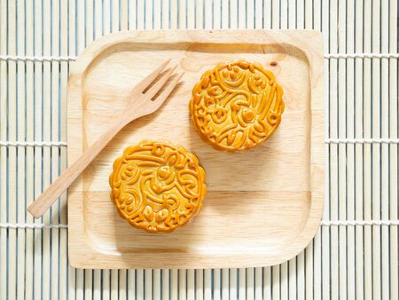 Mooncakes on a wooden plate for Mid-Autumn Festival or Mooncake Festival. Top view.