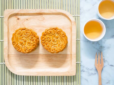 Mooncakes on a wooden plate with cups of tea for Mid-Autumn Festival or Mooncake Festival. Top view. Stockfoto