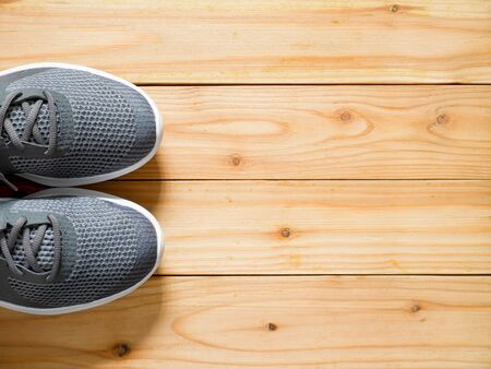 Grey sport shoes on wooden background with copy space